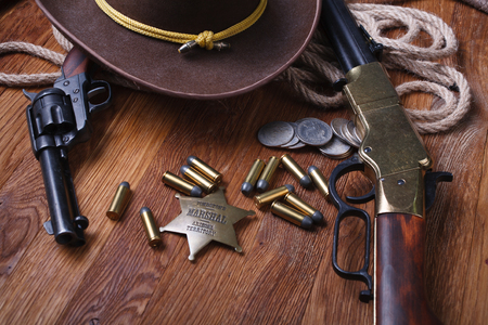 Wild west rifle, ammunition and sheriff badge on wooden table Stock Photo
