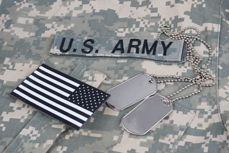 US flag patch with dog tag on Army Combat Uniform background