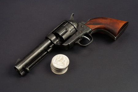 wild west revolver - colt single action army with silver dollars on black background Stock Photo