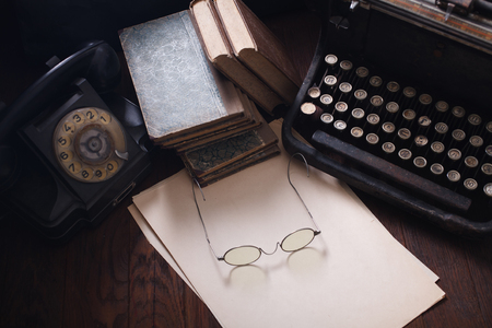 Old retro phone with vintage typewriter and a blank sheet of paper on wooden table Standard-Bild