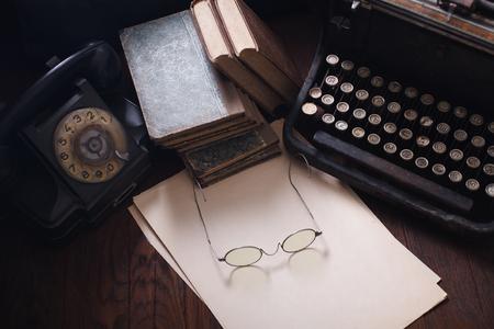 Vecchio telefono retrò con macchina da scrivere vintage e un foglio di carta bianco su un tavolo di legno Archivio Fotografico
