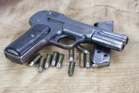 Old rusty handgun with ammunitions on wooden background