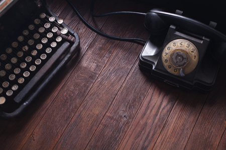 Old retro phone with vintage typewriter and books on wooden table