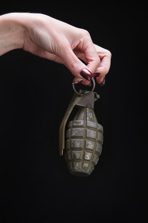 fragmentation grenade in woman hand on black background