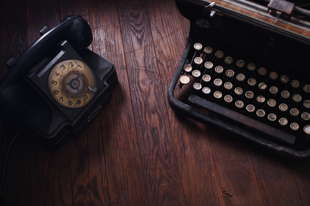 Old retro phone with vintage typewriter on wooden table