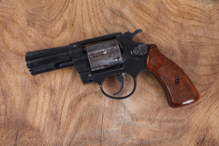 Revolver with ammunition on the wooden background