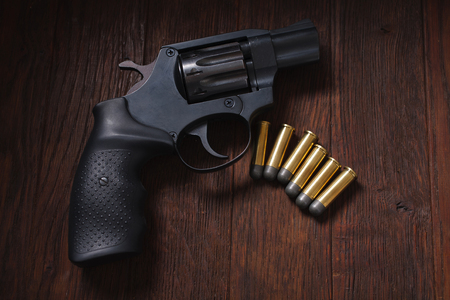 handgun with cartridges on wooden table