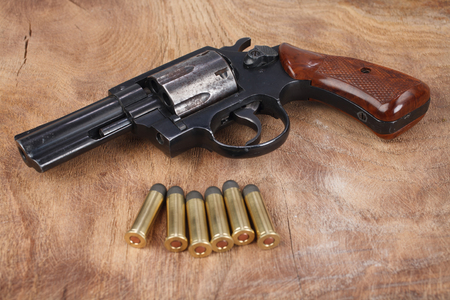 Revolver with ammunition on the wooden background 免版税图像