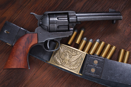 Old revolver with cartridges on wooden table Фото со стока