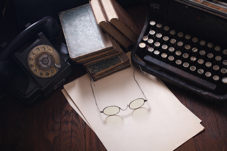 Old retro phone with vintage typewriter and a blank sheet of paper on wooden table Reklamní fotografie