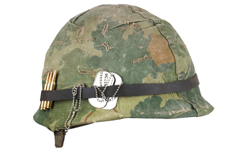 Elmetto dell'esercito americano periodo della guerra del Vietnam con occhiali di protezione mimetici e targhette per cani isolate su bianco