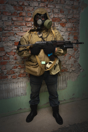 Stalker in gas mask with weapon near the brick wall background 免版税图像