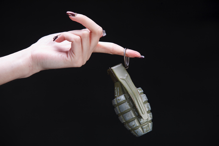 fragmentation grenade in girl hand on black background Imagens