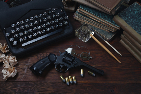 Writing a detective story - old retro vintage typewriter and revolver gun with ammunitions, books, papers, old ink pen on wooden table