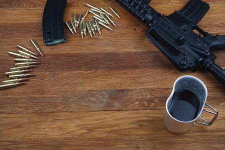 rifle and cup of coffee on wooden table background Stock Photo