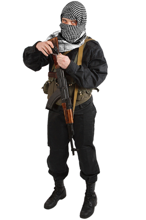 insurgent dressed in black uniform and black and white shemagh with AK 47 rifle isolated on white Archivio Fotografico
