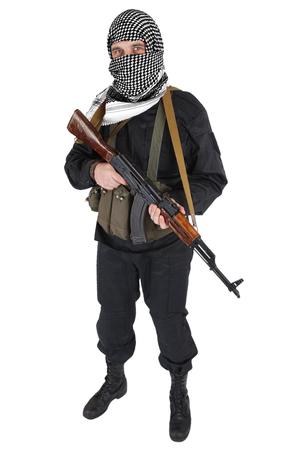 Aufständischer gekleidet in schwarzer Uniform und schwarz-weißem Shemagh mit AK 47-Gewehr isoliert auf weiß