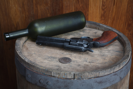 Old western revolver with cartridges and silver dollar on wooden barrel