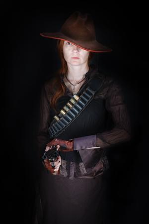 wild west girl with revolver gun on black background
