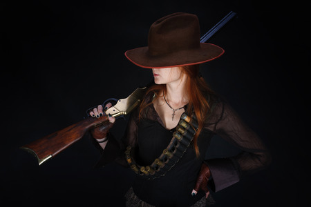 wild west girl with rifle on black background