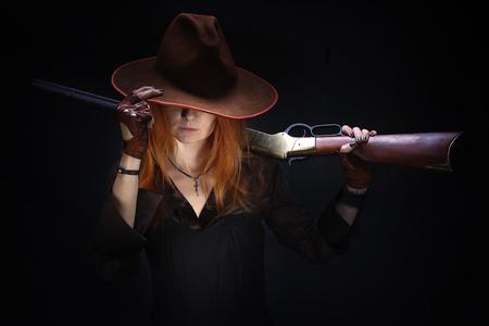 Chica del salvaje oeste con rifle sobre fondo negro Foto de archivo