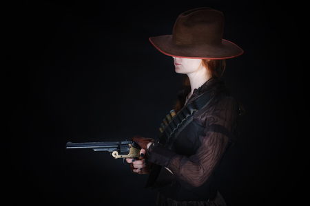 wild west girl with revolver gun on black background