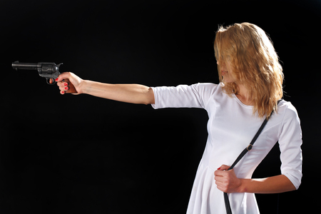 Woman dressed in white with gun on black background