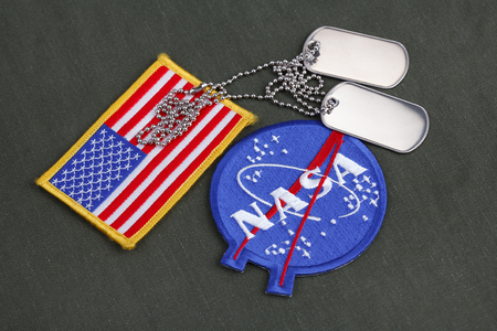 15 March 2018 - The National Aeronautics and Space Administration (NASA) emblem patch and dog tags on green uniform background Editöryel