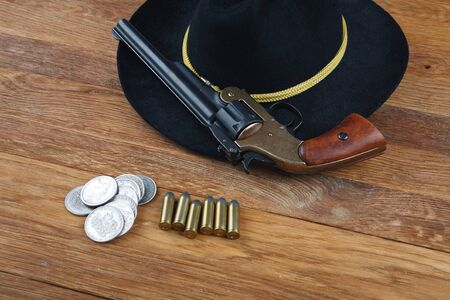 Wild West background - .44 smith and wesson single action revolver gun with cartridges and black hat with silver dollar coins on wooden background Stock Photo