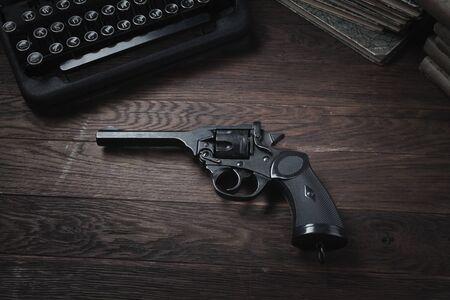 Crime fiction - old retro vintage typewriter and revolver handgun on wooden table