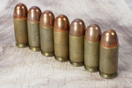 .45 ACP (Automatic Pistol), or .45 Auto (11.43x23mm) a handgun cartridges designed by John Browning in 1905 on wooden background