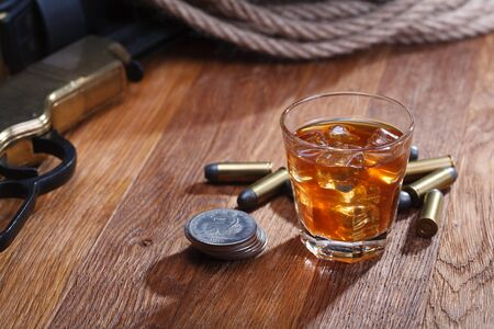 Wild west rifle and ammunitions with glass of whisky and ice with old silver dollar on wooden bar table Stock Photo