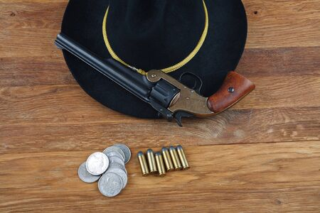 Wild West background - .44 smith and wesson single action revolver gun with cartridges and black hat with silver dollar coins on wooden background Archivio Fotografico