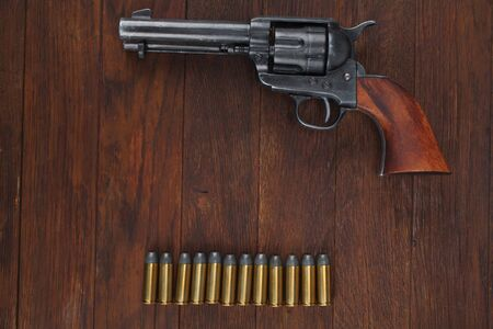 Old revolver with cartridges and U.S. Army soldier's belt with a buckle on wooden table