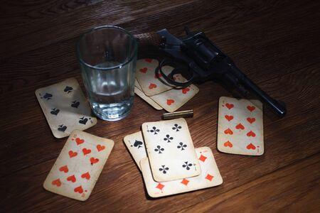 russian roulette - plaing card, glass of vodka and revolver with one cartridge in drum on wooden table background
