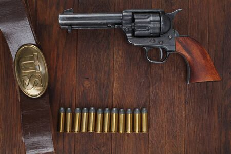 Old revolver with cartridges and U.S. Army soldiers belt with a buckle on wooden table Reklamní fotografie