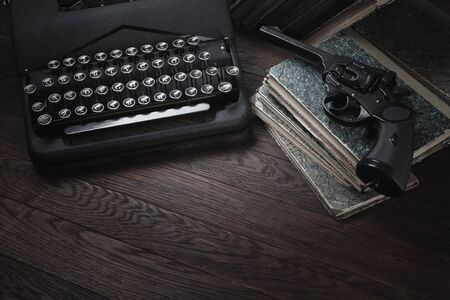 Crime fiction - old retro vintage typewriter and revolver handgun on wooden table