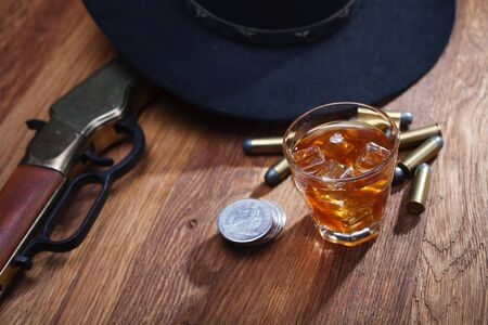 Wild west rifle and ammunitions with glass of whisky and ice with old silver dollar on wooden bar table
