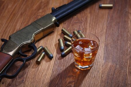 Wild west rifle and ammunitions with glass of whisky and ice on wooden bar table