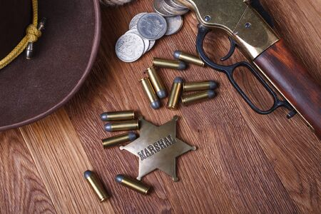 Wild west gun, ammunition and U.S. Marshal Badge on wooden table