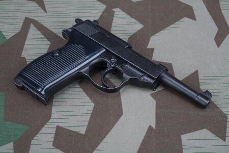 Pistola semiautomática de 9 mm del ejército alemán de la segunda guerra mundial sobre fondo uniforme camuflado