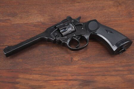 Mk IV Top-Break Revolver service pistol for the armed forces of the United Kingdom, and the British Empire and Commonwealth on wooden table
