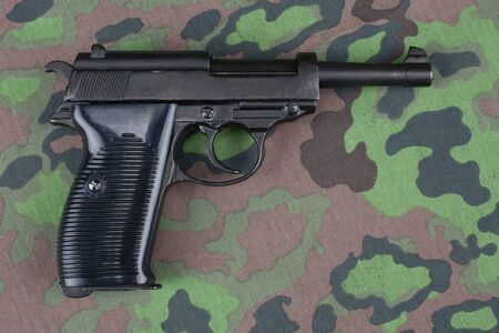 WWII era german army 9 mm semi-automatic pistol on camouflaged uniform background