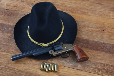 Wild West background - .44 smith and wesson single action revolver gun with cartridges and black hat on wooden background