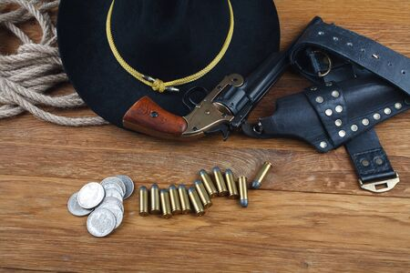 Wild West background - .44 smith and wesson single action revolver gun with cartridges and black hat with silver dollar coins on wooden background Stok Fotoğraf