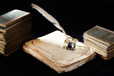 Old vintage fountain pen, books and inkwell on a black textured background Фото со стока