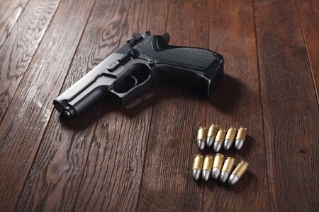 illegal handgun with cartridges on wooden table