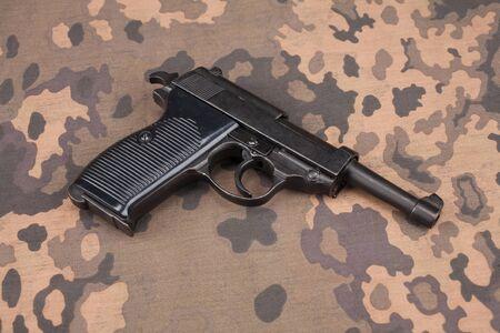 Pistolet semi-automatique de 9 mm de l'armée allemande de l'époque de la Seconde Guerre mondiale sur fond uniforme camouflé