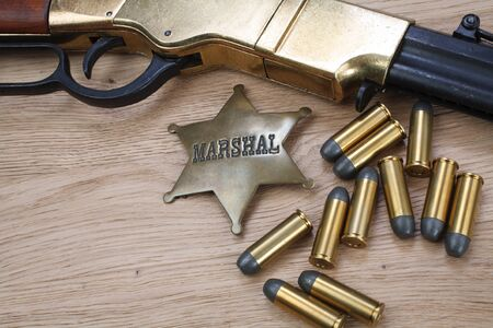 Wild west gun with ammunition and marshal badge on wooden background
