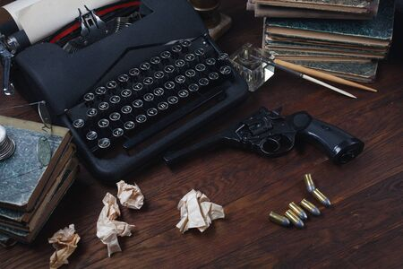 Writing a crime fiction story - old retro vintage typewriter and revolver gun with ammunitions, books, papers, old ink pen on wooden table 스톡 콘텐츠